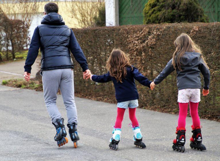Pai e duas meninas andando de patins.