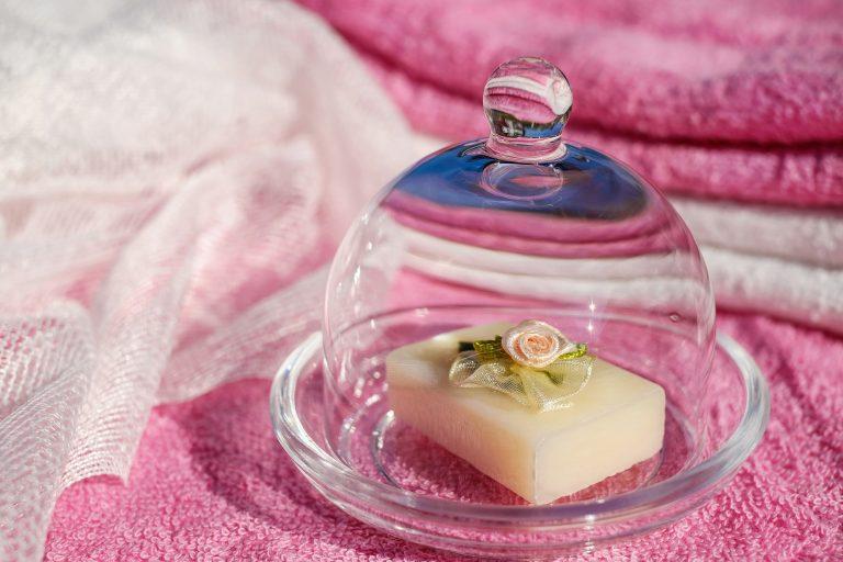 Foto de um sabonete em barra com uma flor artificial em cima, dentro de uma saboneteira de vidro.