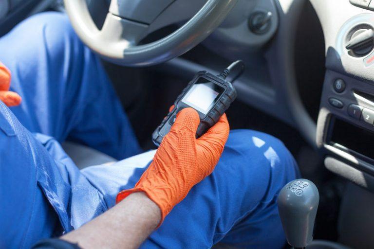 Imagem mostra um pequeno scanner automotivo conectado a um carro.