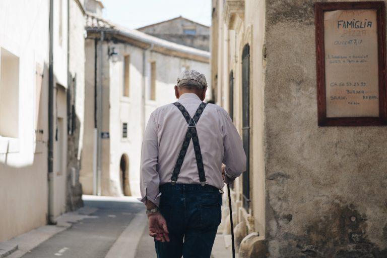 Imagem mostra um homem de idade andando de costas e usando um suspensório.
