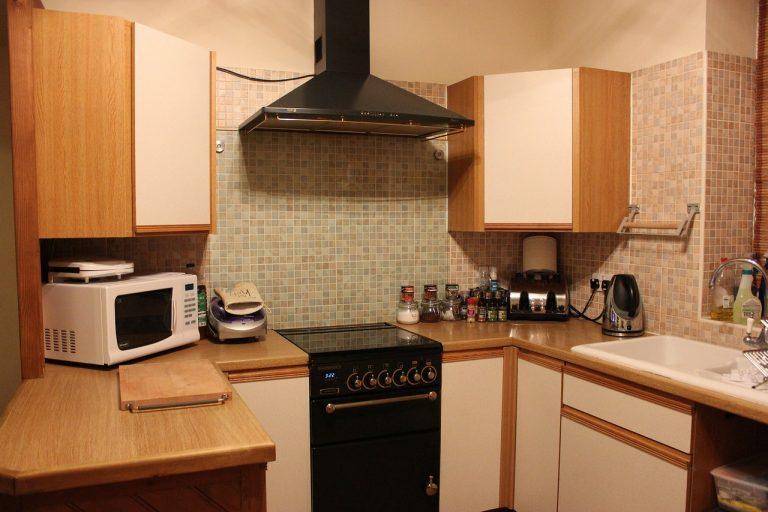 Imagem mostra uma cozinha toda decorada com um forno micro-ondas e outros eletrodomésticos.