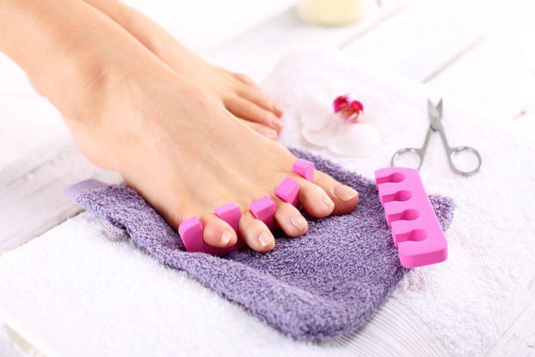 Imagem de pé feminino fazendo pedicure apoiado em toalha com tesourinha ao lado