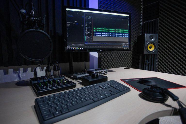 Imagem mostra a mesa de trabalho de um estúdio de gravação de áudio. Na mesa, estão, além de uma mesa de som de 4 canais, um monitor, um teclado e outros operadores e controladores. Há ainda um microfone, pendurado sobre a mesa.