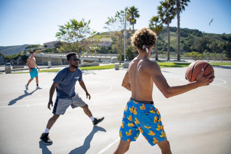 Imagem mostra o momento de um jogo de meia quadra num parque. Um jogador, sem camisa e de costas para a câmera, que segura a bola, é marcado por um homem de óculos escuros. Ao fundo, outro jogador sem camisa, desfocado.