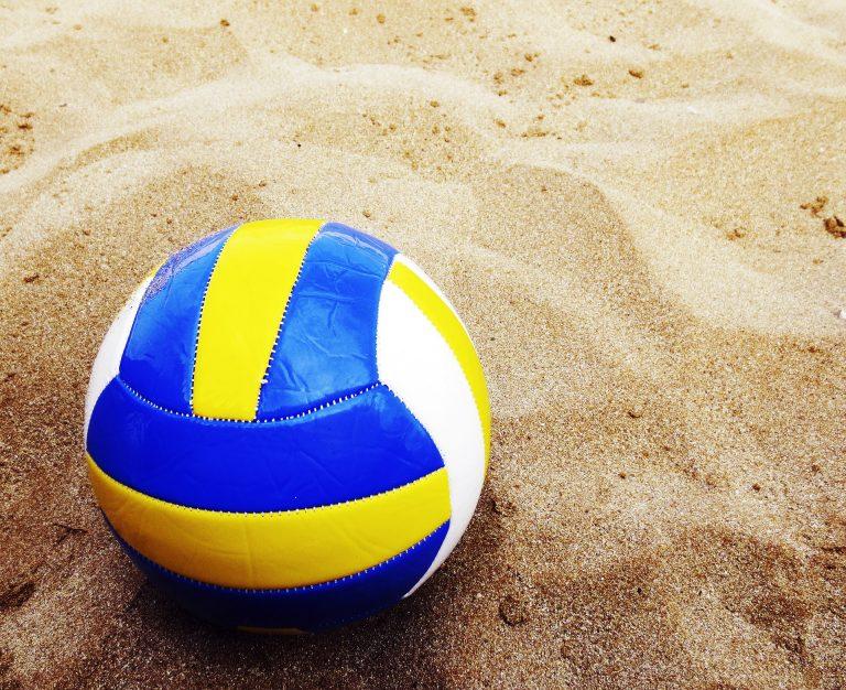 Na foto uma bola de vôlei amarela, branca e azul na areia de uma praia.