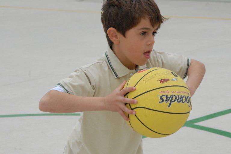 Na foto um menino segurando uma bola de basquete dentro de uma quadra.