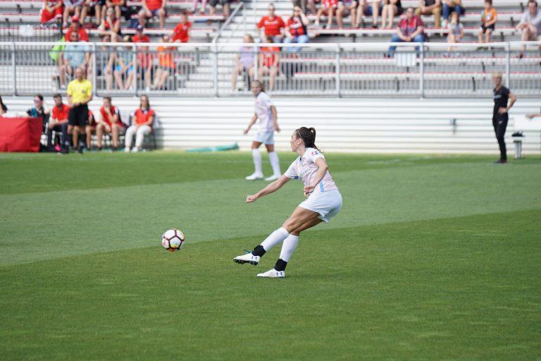 Imagem mostra uma jogadora durante um jogo de futebol. Ela usa chuteiras brancas da Mizuno, e está chutando a bola.