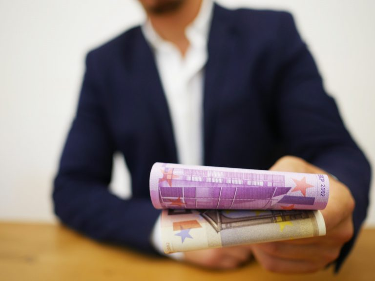 Homem entregando notas de dinheiro.