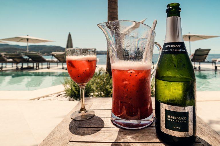 Na foto uma jarra de vidro ao lado de uma garrafa e uma taça em frente a uma piscina.