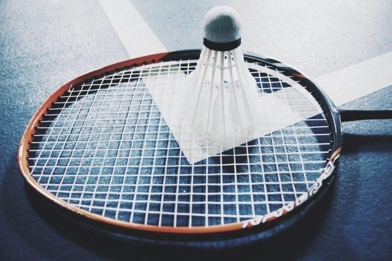 Imagem mostra um close de uma peteca repousando, com as penas para baixo, sobre os fios de uma raquete de badminton.
