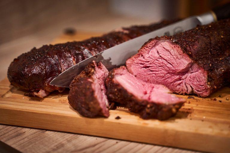 Imagem de faca junto de carne cortada sobre tábua de madeira