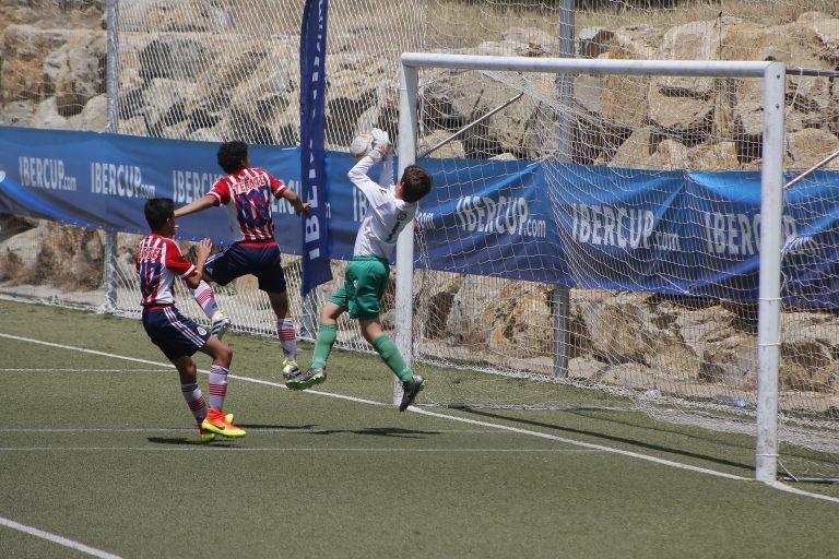 Imagem mostra um jovem goleiro, usando luvas Adidas, agarrando uma bola durante um jogo de futebol.