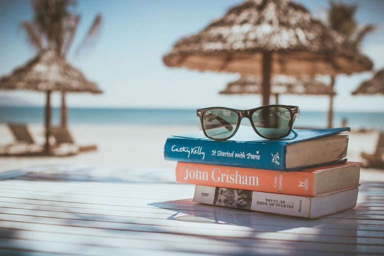 Na foto três livros em cima de uma mesa com uma praia ao fundo.