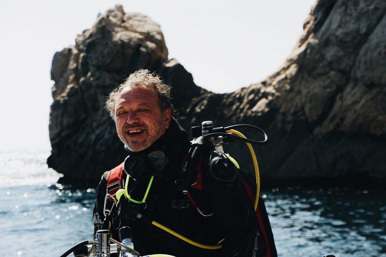 Imagem mostra um homem com a roupa de mergulho completa, mas com a máscara abaixada. Ele sorri, com o mar e uma formação rochosa ao fundo.