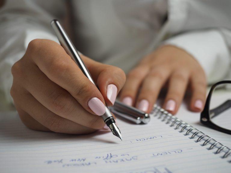 Imagem de uma pessoa escrevendo.