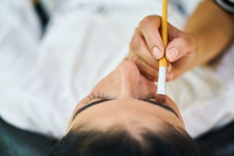 Na foto uma pessoa com o pincel na sobrancelha de outra.