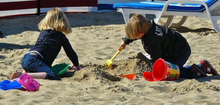 Imagem de crianças brincando com brinquedos de praia na areia