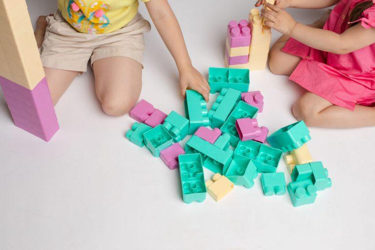 Na foto um bebê brincando com cubos de montar com uma mulher o segurando.