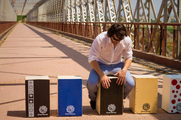 foto de um homem em uma ponte com 5 cajons diferentes um ao lado do outro.