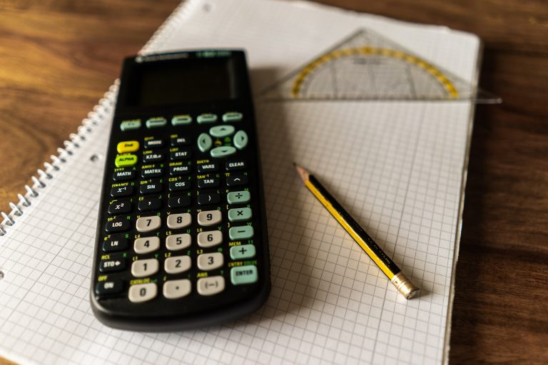 Calculadora apoiada sobre caderno ao lado de lápis e esquadro