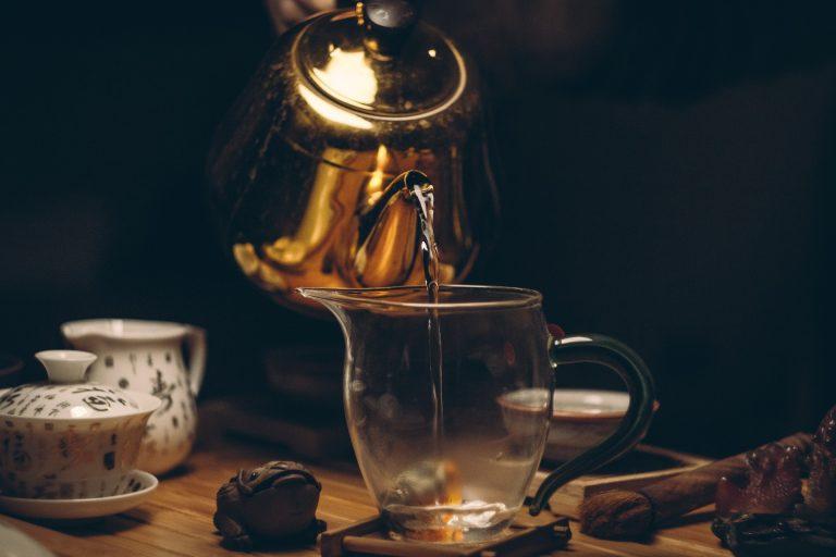 Pessoa servindo água com a chaleira para fazer chá.