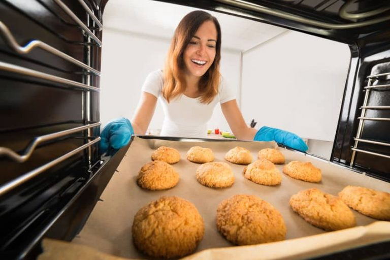 Na foto uma mulher tirando uma assadeira de biscoitos de dentro de um forno.