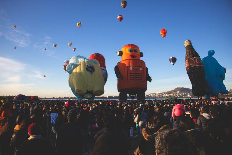 Imagem mostra o que parece ser um desfile, com pessoas amontoadas no plano baixo, olhando para os grandes bonecos infláveis, no plano baixo.