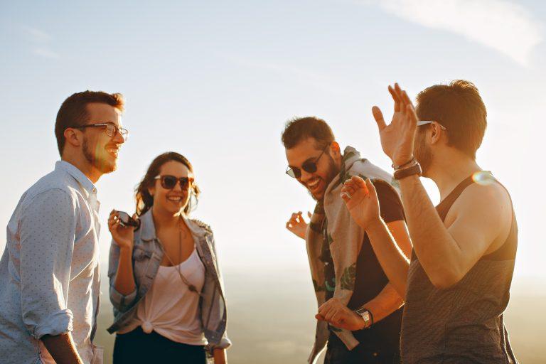Imagem mostra um grupo de amigos se divertindo ao ar livre, sob uma clara e leve luz solar.