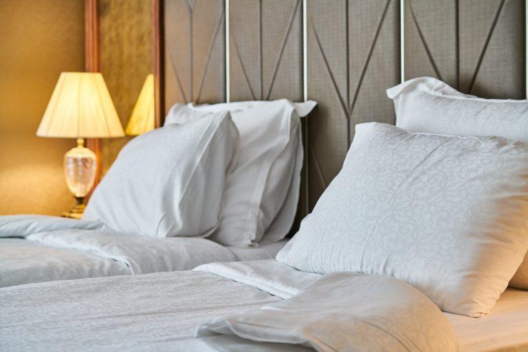 Foto de duas camas de solteiro arrumadas, com travesseiros e roupa de cama branca.