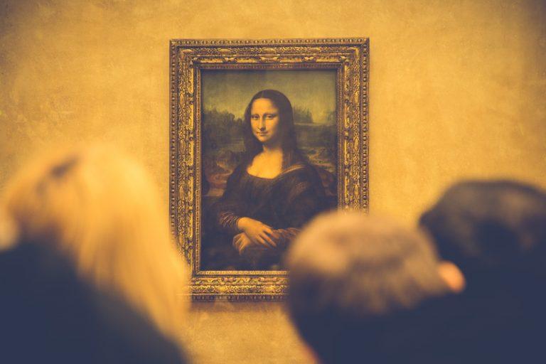 """Imagem mostra o quadro de Leonardo Da Vinci, """"Monalisa"""", exposto no Museu do Louvre, e parcialmente encoberto por cabeças de visitantes, desfocadas na foto.."""