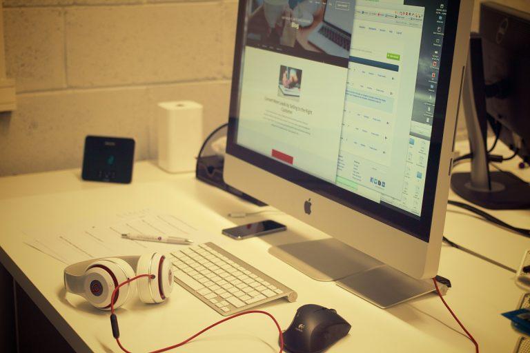 Computador na mesa de trabalho com fone de ouvido e mouse.