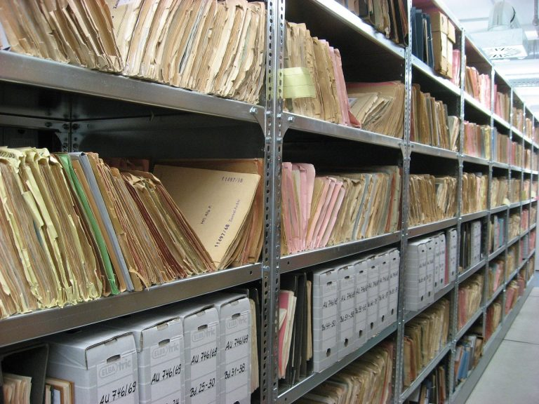 Imagem de várias pastas sanfonadas organizadas em estantes de arquivo
