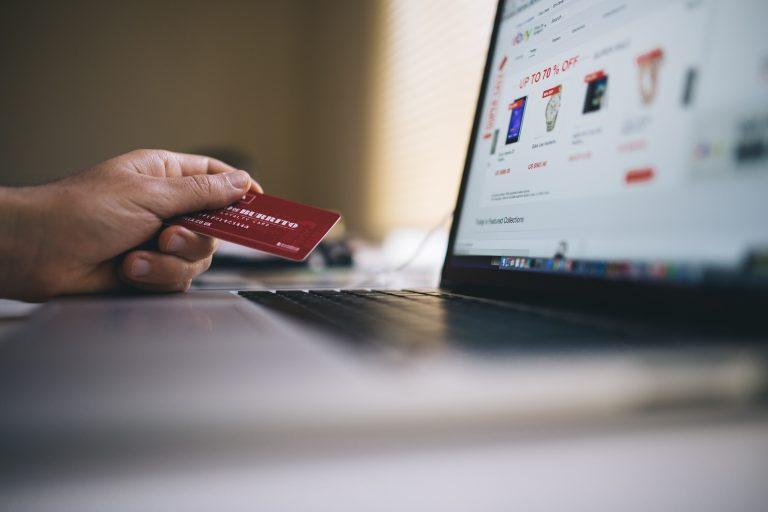 Na foto um homem com um cartão de crédito na mão usando o computador.