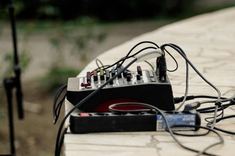 Imagem mostra uma mesa de som sobre um palco de pedra. Ela está ligada e toda conectada em cabos e tomadas.