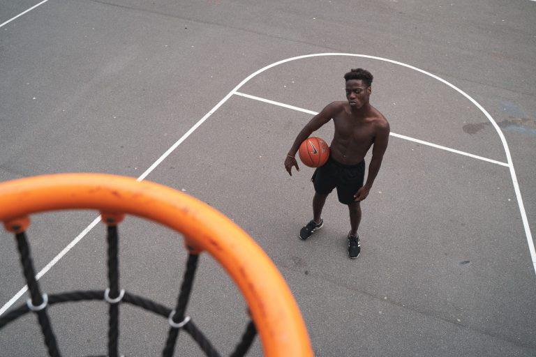 Imagem tem a câmera na altura da tabela de uma quadra de basquete, e mostra um jogador, sem camisa e com uma bola de basquete Nike apoiada na cintura, posando no garrafão da quadra.