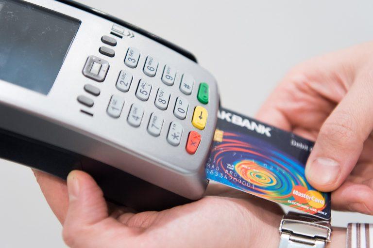 Pessoa passando cartão de crédito em maquininha de pagamento.