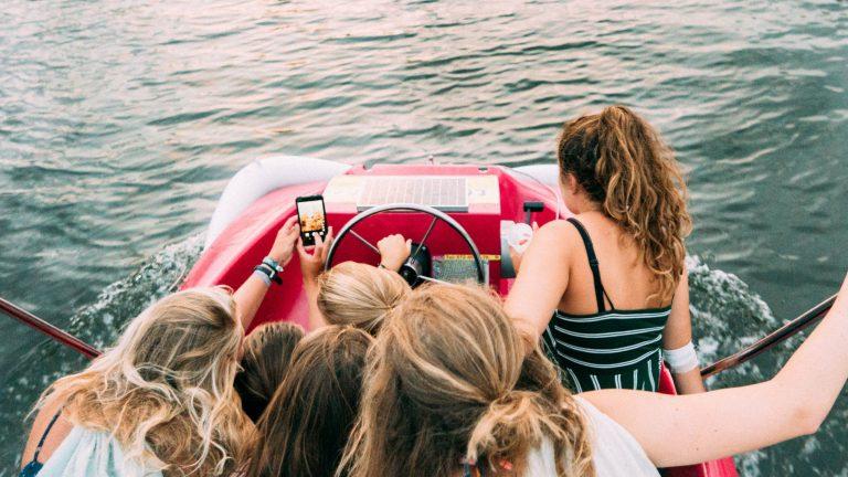 Mulheres em lancha com celular.