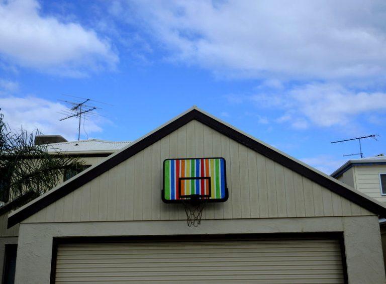 Na foto uma cesta de basquete infantil instalada na frente de uma casa.