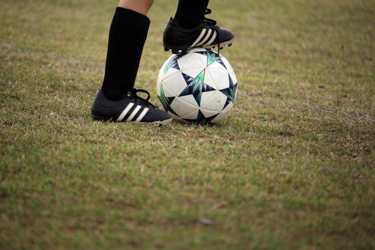 Imagem mostra um close dos pés de uma criança, que calça chuteiras com travas e domina uma bola de futebol na sola do pé direito.