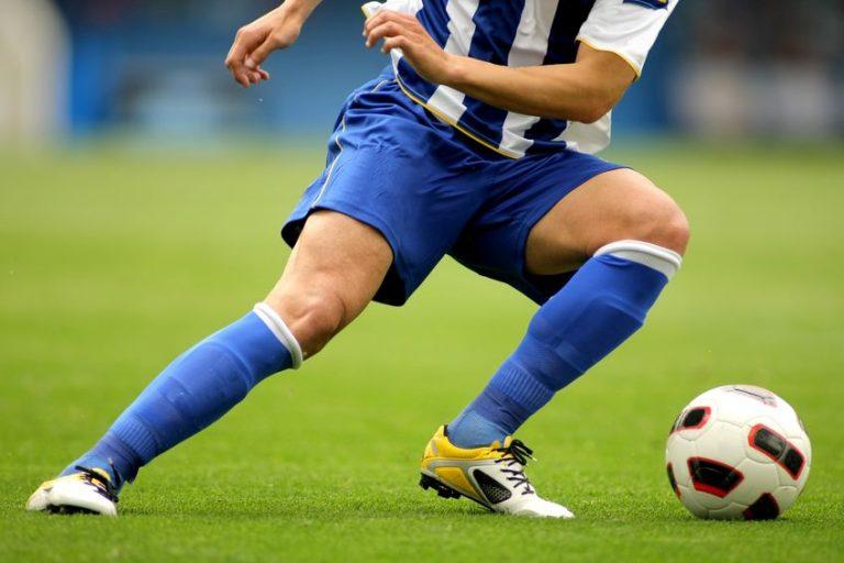 Imagem mostra o close das pernas e chuteiras de um jogador de futebol durante um jogo. Ele está mudando de direção, e tem a bola próxima ao seu pé esquerdo.