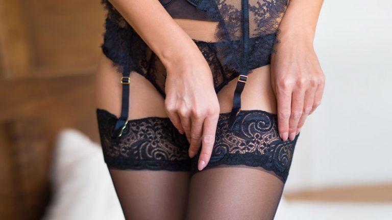 Imagem de mulher ajustando a altura de uma cinta liga preta