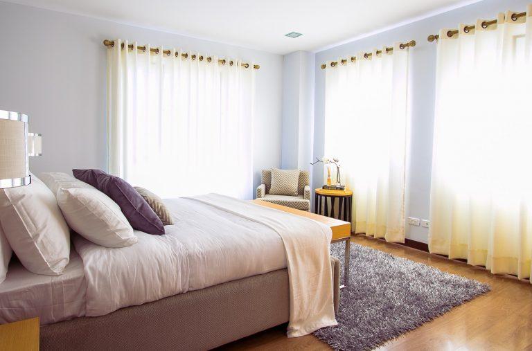 Na foto um quarto de casal com cortinas, tapete e almofadas em cima da cama.