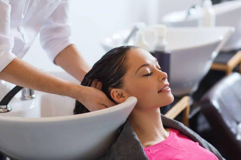 Na foto uma mulher em um lavatório de cabeleireiro.