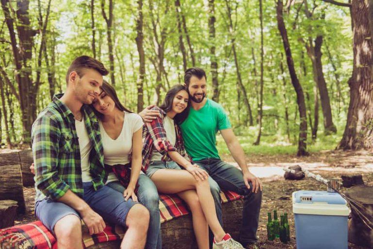 Na foto dois casais ao ar livre sentados em um tronco de madeira perto de um cooler.