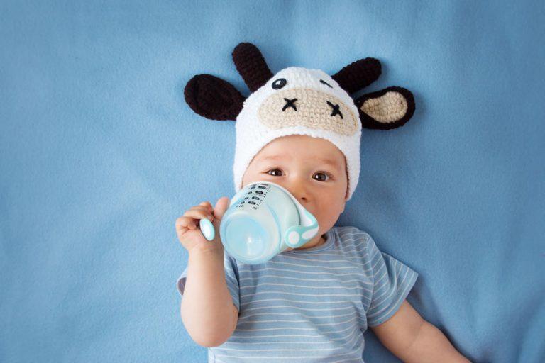 Imagem de uma criança tomando leite num copo antivazamento.