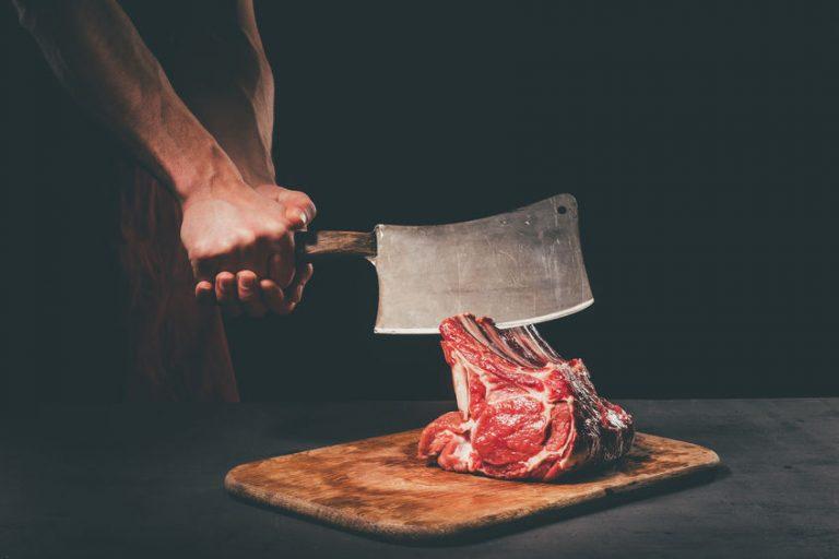 Imagem de um homem cortando uma peça de carne.