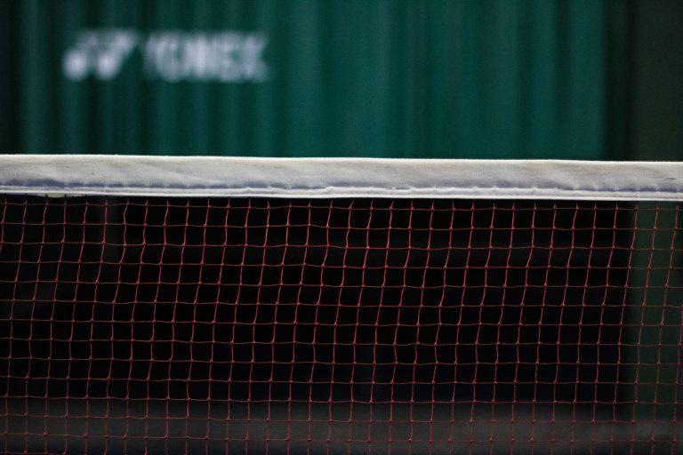 Imagem mostra, em foco seletivo, o pedaço de uma rede esportiva, mostrando seus fios quadriculados e a fita branca acima deles.