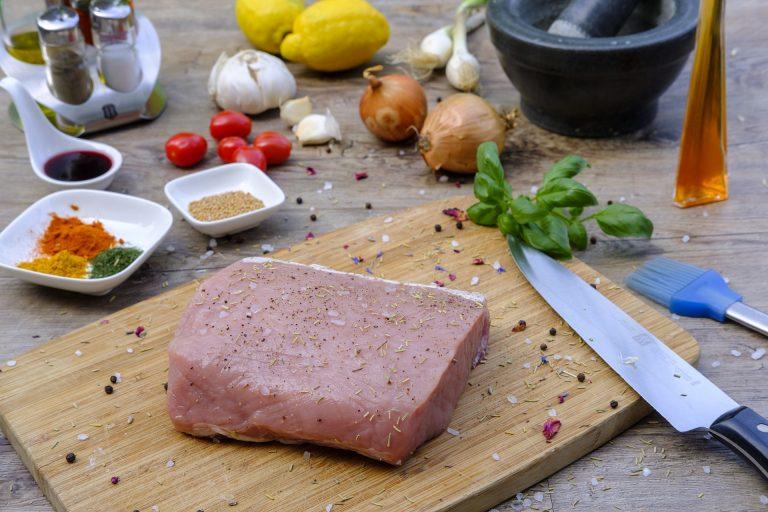 Imagem de faca junto de carne temperada sobre tábua de madeira