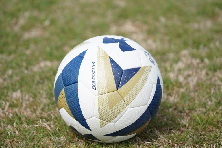 Imagem mostra o close de uma pequena bola de futebol. É possível observar os detalhes do design da bola, como sua textura, cores e padrões de estampa.