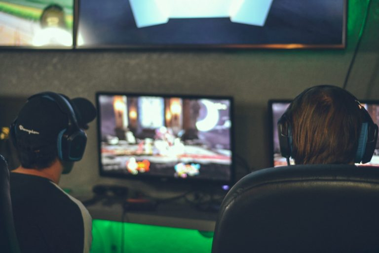 Image of two people playing on gamer monitors
